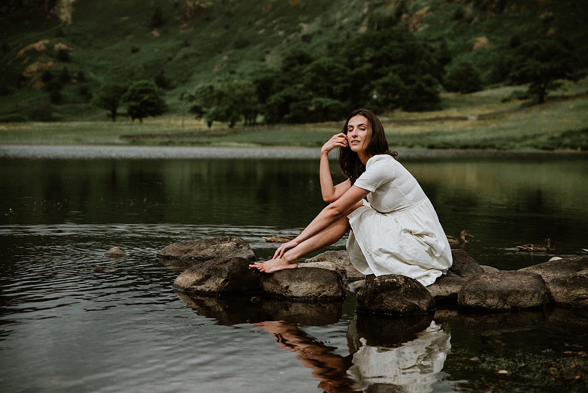 Crouched on a rock at the waters edge, the woman looks thoughtful at Blea Tarn, Lake District, Cumbria during lake district photography portrait shoot by lake district wedding photographer
