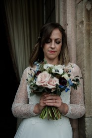 Bride looking at her flowers at Askham Hall, Cumbria