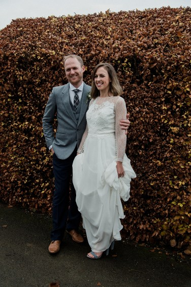 Bride and groom in front of autumn hedge at Askham Hall