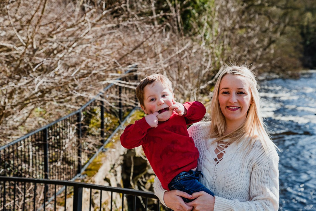 Hands in his mouth, the little boy pulls a funny face while mummy holds him safe and tight during our North East lifestyle portrait engagement photography shoot at Barnard Castle, Teesdale, County Durham
