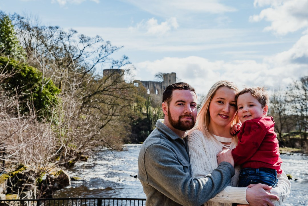 The loving couple pose in front of the castle during our North East lifestyle portrait engagement photography shoot at Barnard Castle, Teesdale, County Durham