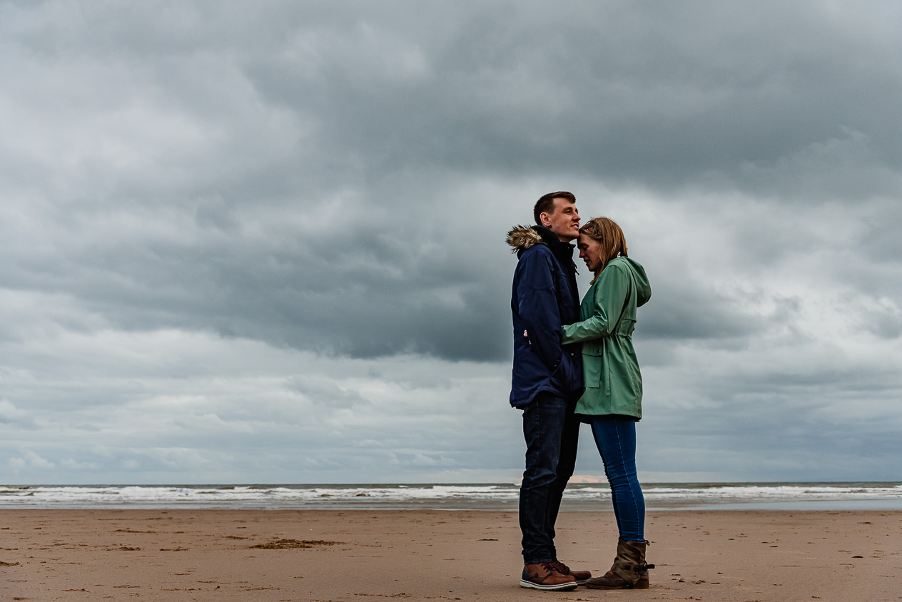 As the man looks out to the shoreline, his fiancee cuddles up close to steal his warmth during St Bees engagement photography shoot at St Bees, Cumbria by lake district wedding photographer