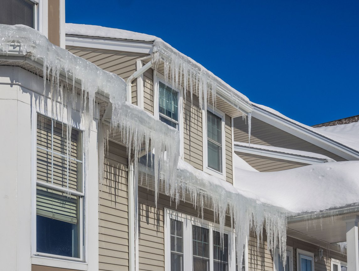 icicles on the eave of a white home