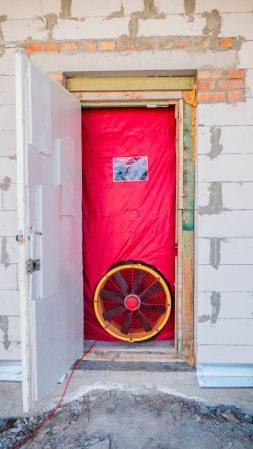 blower door test on front door of a house