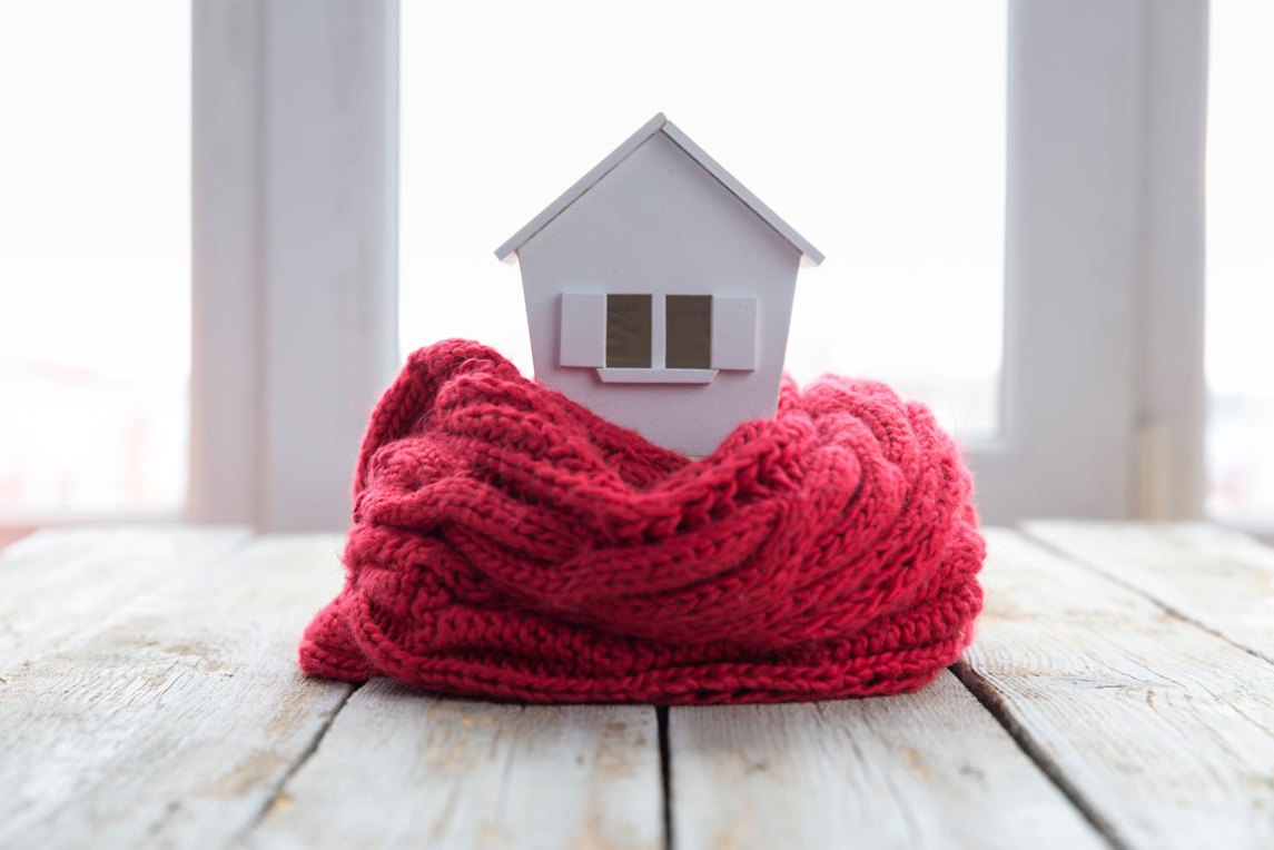 red quilt wrapped around model house