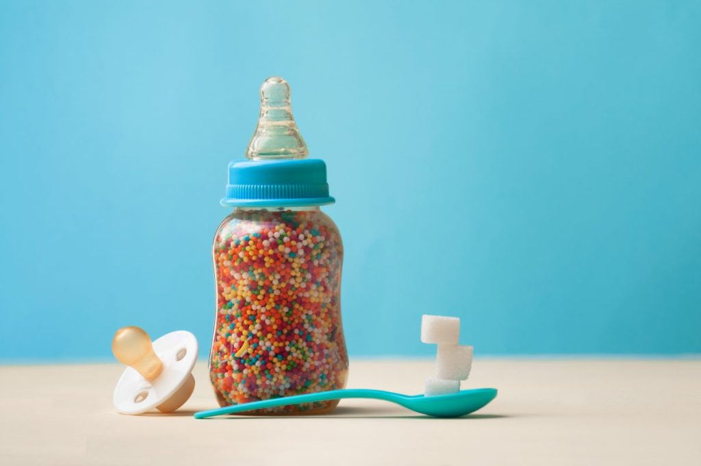 Baby bottle filled with sugar sprinkles to show unhealthy food