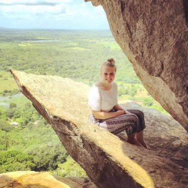 Hannah sat on the edge of Mihintale rock, above rainforest and a long, long drop.