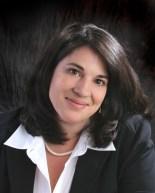 headshot, shoulder length dark hair and dark eyes, wearing a suit