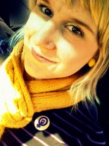 Kristen, smiling with yellow scarf and blond hair