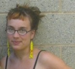 Stephanie Dank, with glasses and long yellow earrings