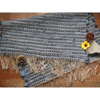Dark Blue woven floor rug made with cut denim jeans folded over with a yellow flower on top.