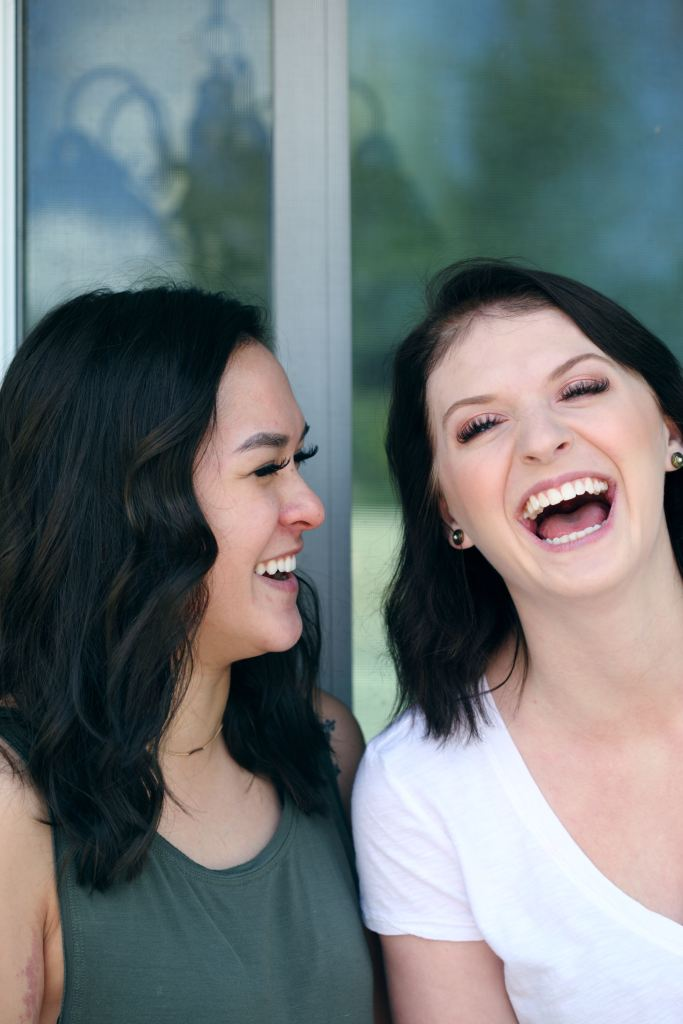 women laughing, comparing and competing