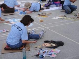 Une artiste dessine sur le trottoir