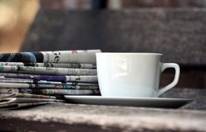 Tasse de café à côté d'une pile de journaux