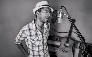 Chanteur au micro avec une guitare posée à ses côtés