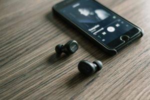 Paire d'écouteurs Bluetooth à côté d'un téléphone