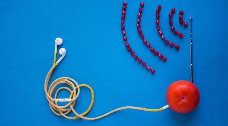 Des écouteurs blancs branchés à une tomate avec une antenne