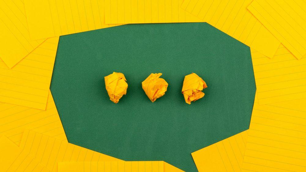 Trois boules de papier froissées sur une surface verte entourés de papier ligné jaune