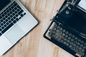 Un ordinateur portable moderne à côté d'une vieille machine à écrire