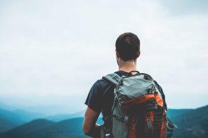Un homme avec un sac à dos au sommet d'une montagne