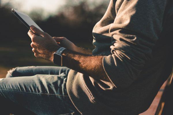 Une personne assise sur une chaise avec une tablette tactile