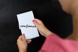 Une femme tient un carnet avec le mot confiance inscrit dessus