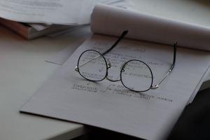 Des lunettes posées sur un carnet de notes