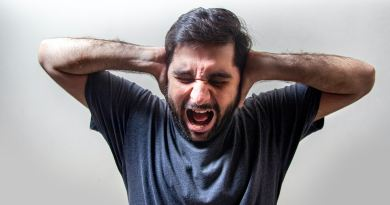 Un homme en panique avec les mains sur les oreilles