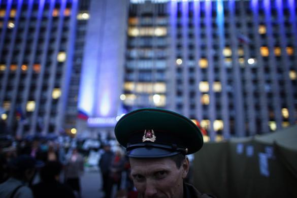A man wearing a Soviet military hat poses for a picture outside a regional government building in Donetsk