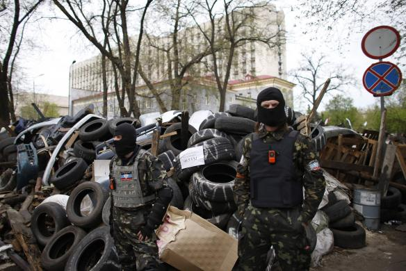 Masked pro-Russia protesters stand guard at a barricade outside a regional government building in Donetsk