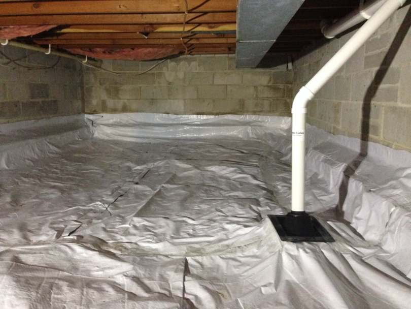 A crawlspace with a poly liner and a radon mitigation system pipe.