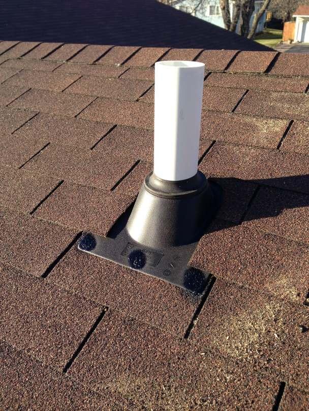 Radon mitigation system vent pipe going through a asphalt shingle roof.