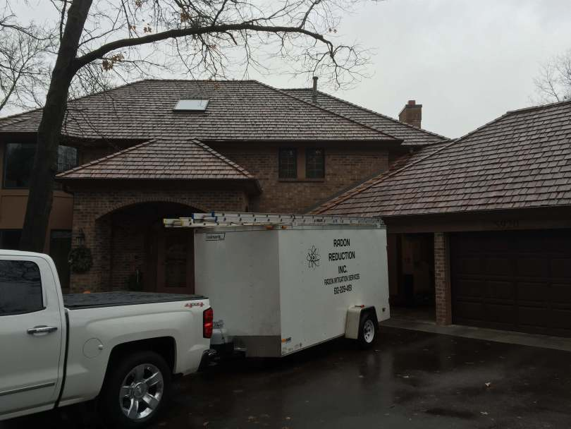 Radon Reduction trailer in front of a two story house.