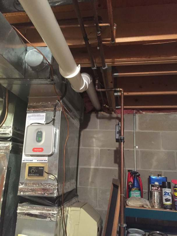 A radon pipe is run through a chase between a basement bathroom ceiling and the floor joists, as part of a radon mitigation system.