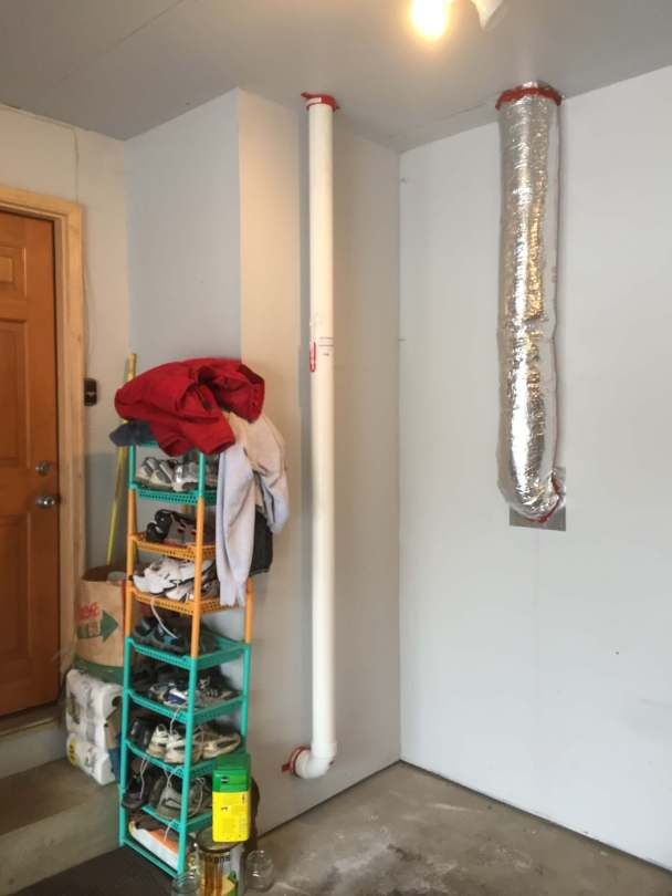 A radon vent pipe is run through a garage with a fire collar at each end, as part of a radon mitigation system.