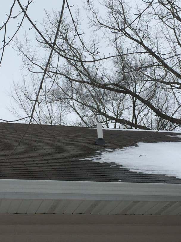 A radon vent exiting a garage roof