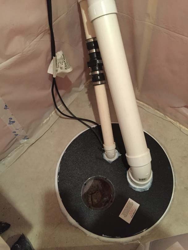 A sealed sump lid with a radon vent pipe and sump pump pipe coming out.