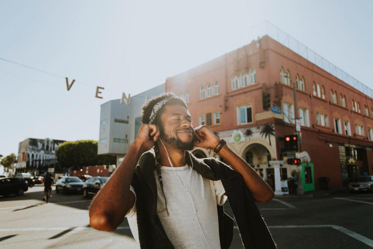 Jovem negro unindo música em fones de ouvido em frente a um prédio de tijolos aparentes. Pixels.com