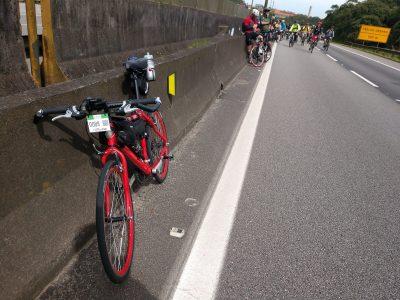 Bicicleta vermelha encostada ao lado de uma estrada