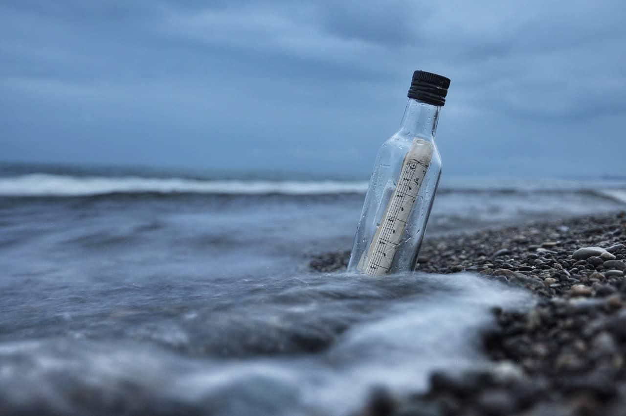 Papel enrolado dentro de uma garrafa de vidro na areia da praia