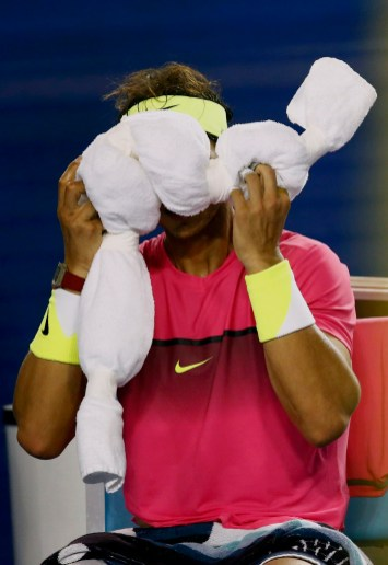Nadal of Spain applies an ice-pack to his face during his men's singles second round match against Smyczek of the U.S. at the Australian Open 2015 tennis tournament in Melbourne