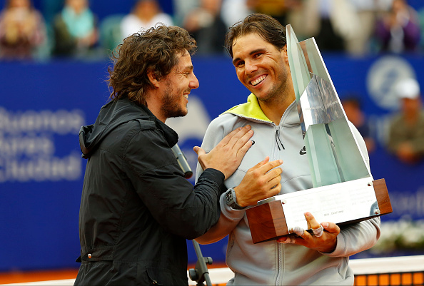 BUENOS AIRES, ARGENTINA - MARCH 01:  Rafael Nadal of Spain receives the trophy from former tennis player Gaston Gaudio after wining the singles final match between Rafael Nadal of Spain and Juan Monaco of Argentina as part of ATP Argentina Open at Buenos Aires Lawn Tennis Club on March 01, 2015 in Buenos Aires, Argentina. (Photo by Gabriel Rossi/LatinContent/Getty Images)