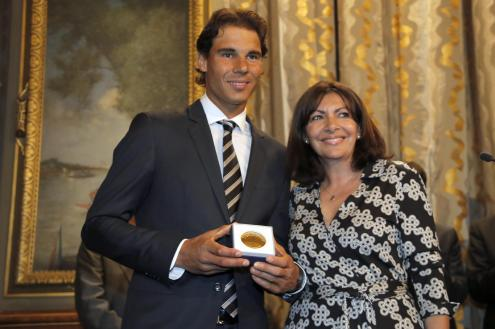 Tennis player Rafael Nadal poses with the Grand Vermeil Paris medal, he received from Paris Mayor Anne Hidalgo, right, during a ceremony at the Paris city Hall, in Paris, France, Thursday, May 21, 2015. By winning the 2014 French Open, Nadal became the only male player to win a single Grand Slam tournament nine times and he begins the defense of his title for the upcoming French Open at Roland Garros stadium next week. (AP Photo/Francois Mori)