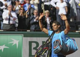 Spain's Rafael Nadal waves goodbye to spectators as he leaves center court while Serbia's Novak Djokovic celebrates winning the quarterfinal match of the French Open tennis tournament in three sets, 7-5, 6-3, 6-1, at the Roland Garros stadium, in Paris, France, Wednesday, June 3, 2015. (AP Photo/David Vincent)