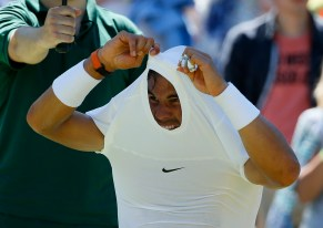 Rafael Nadal of Spain struggles to take his shirt off during a break between games of his match against Thomaz Bellucci of Brazil at the Wimbledon Tennis Championships in London, June 30, 2015. REUTERS/Stefan Wermuth