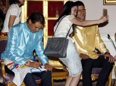 A Thai woman takes selfie photo with tennis players Novak Djokovic, right, of Serbia next to Rafael Nadal of Spain at Government House in Bangkok, Thailand Friday, Oct. 2, 2015. Djokovic will face Nadal in the tennis exhibition match in Bangkok to boost confidence in Thailand's safety after a deadly Aug. 17 bombing that left 20 dead in the heart of the capital. (Rungroj Yongrit/Pool Photo via AP)