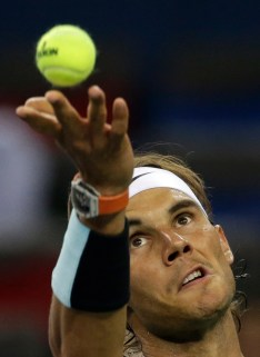 Rafael Nadal of Spain tosses the ball as he plays against Milos Raonic of Canada during their Shanghai Masters tennis tournament in Shanghai, China, Thursday, Oct. 15, 2015. (AP Photo/Andy Wong)