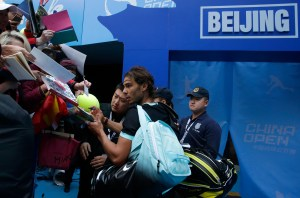 Rafael Nadal of Spain autographs to spectators after winning the men's singles semifinals match against Fabio Fognini of Italy in the China Open tennis tournament at the National Tennis Stadium in Beijing, Saturday, Oct. 10, 2015. (AP Photo/Andy Wong)