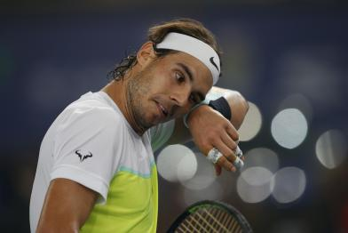 Rafael Nadal of Indian Aces wipes the sweat from his face as he plays Roger Federer of UAE Royals in the men's singles event of the International Premier Tennis League in New Delhi, India, Saturday, Dec. 12, 2015. (AP Photo /Tsering Topgyal)