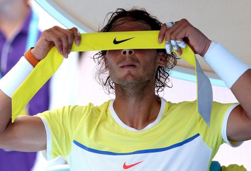 Rafael Nadal of Spain changes his head band during his first round loss to compatriot Fernando Verdasco during their first round match at the Australian Open tennis championships in Melbourne, Australia, Tuesday, Jan. 19, 2016.(AP Photo/Aaron Favila)